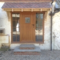 New front door with newly constructed porch roof and steps